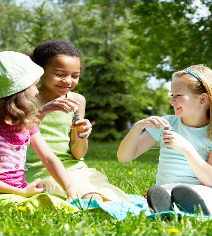 Girls blowing bubbles in green grass on sunny summer day