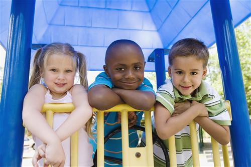 3 children on playground equipment, smiling