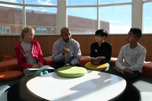 Falcon Creek principal and students discuss a book in their new innovation space