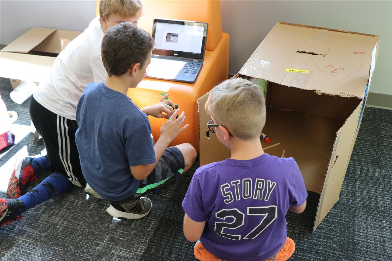 A team of three boys park on the floor in the library to colaborate on their cardboard project.
