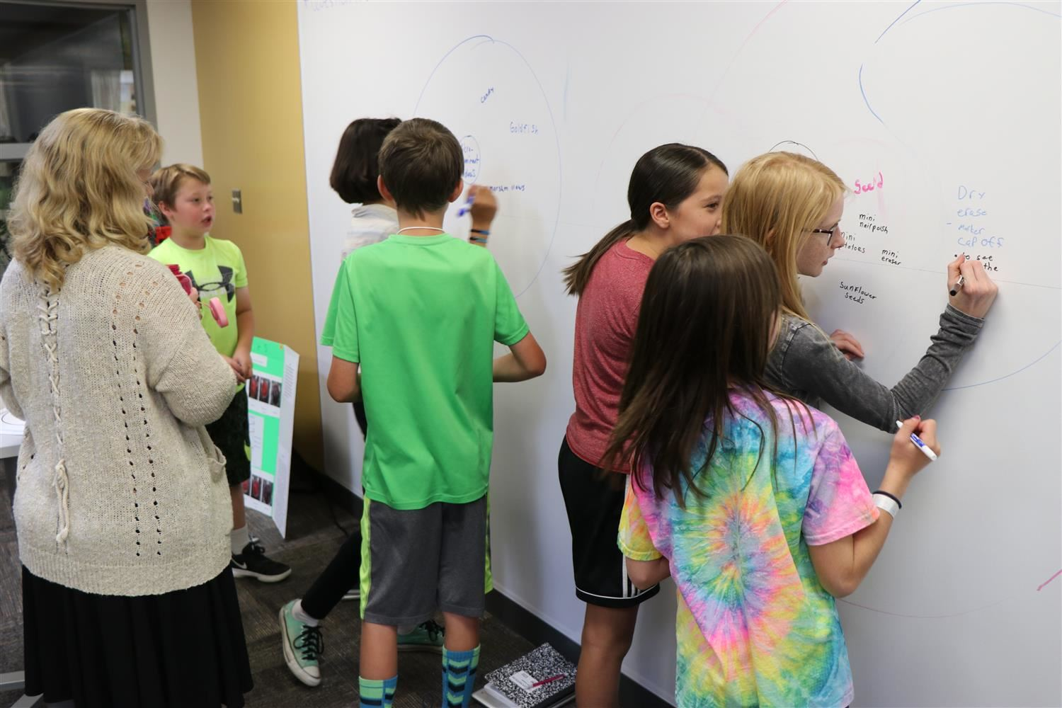 Six different students record answers on a floor-to-wall dry erase board.