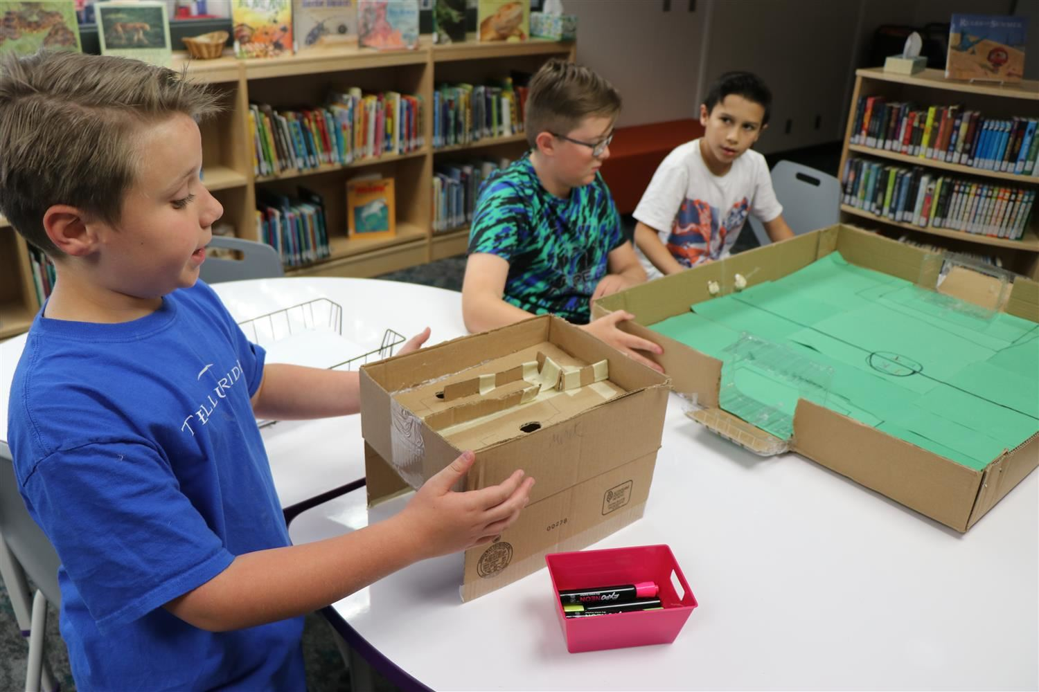 Three boys work on the Cardboard Challenge in their newly renovated library.