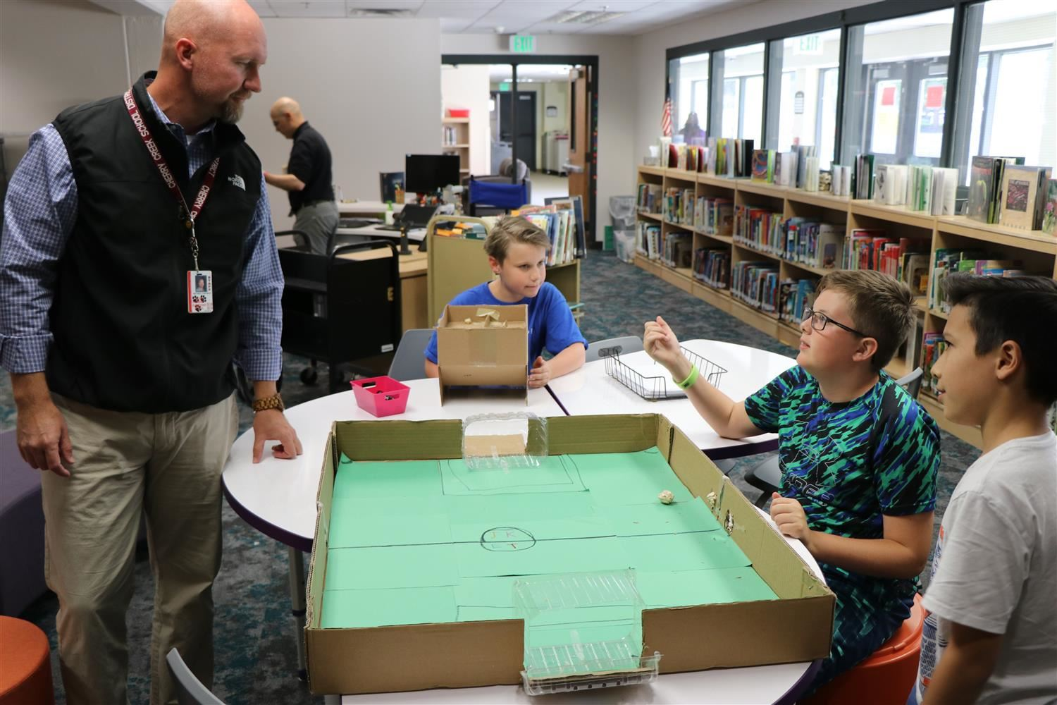 Principal Mike Chapman talks to students about a cardboard stadium they created in their newly renovated library.