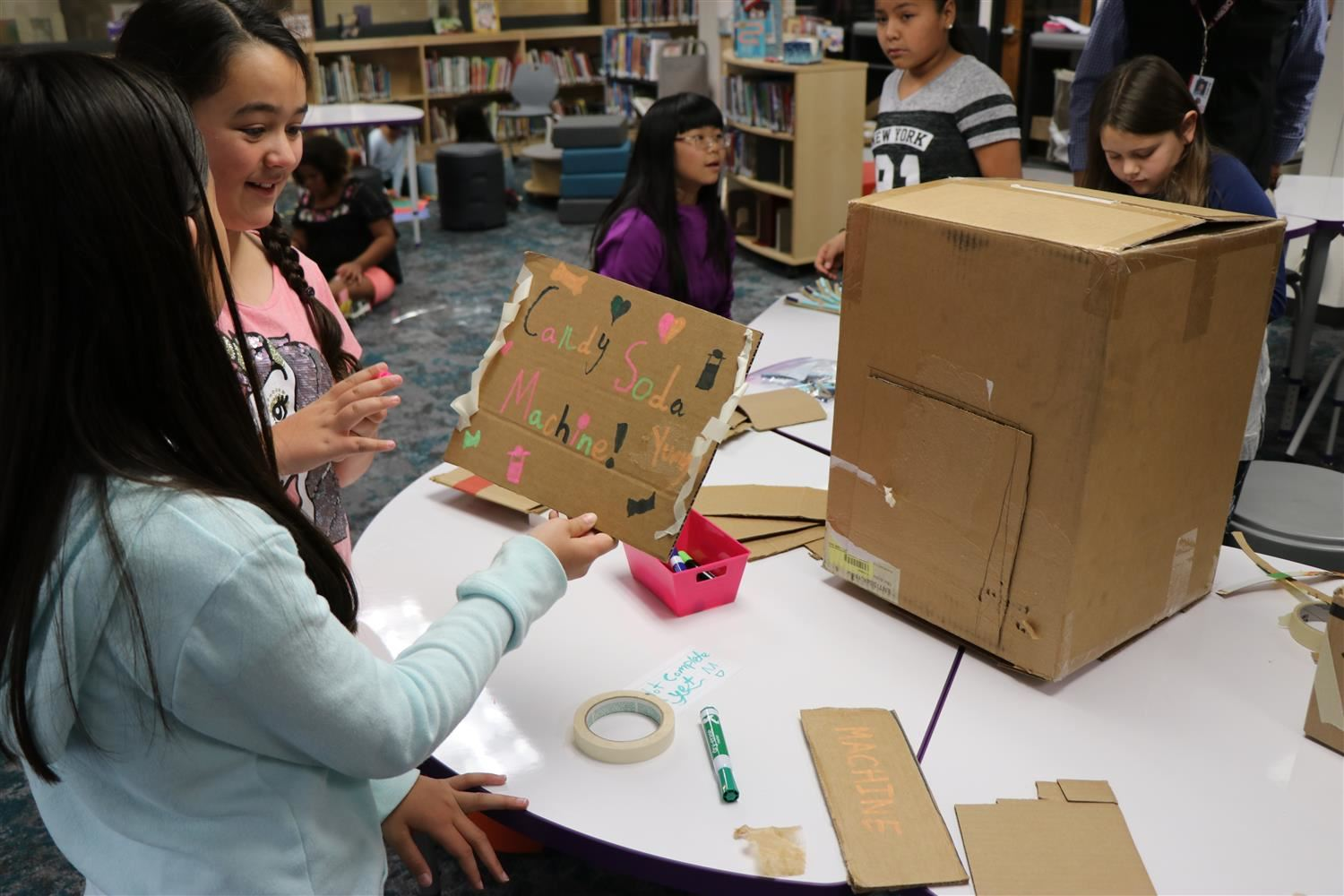 Two partners work on their Candy Soda Machine they created out of cardboard in the newly renovated library.