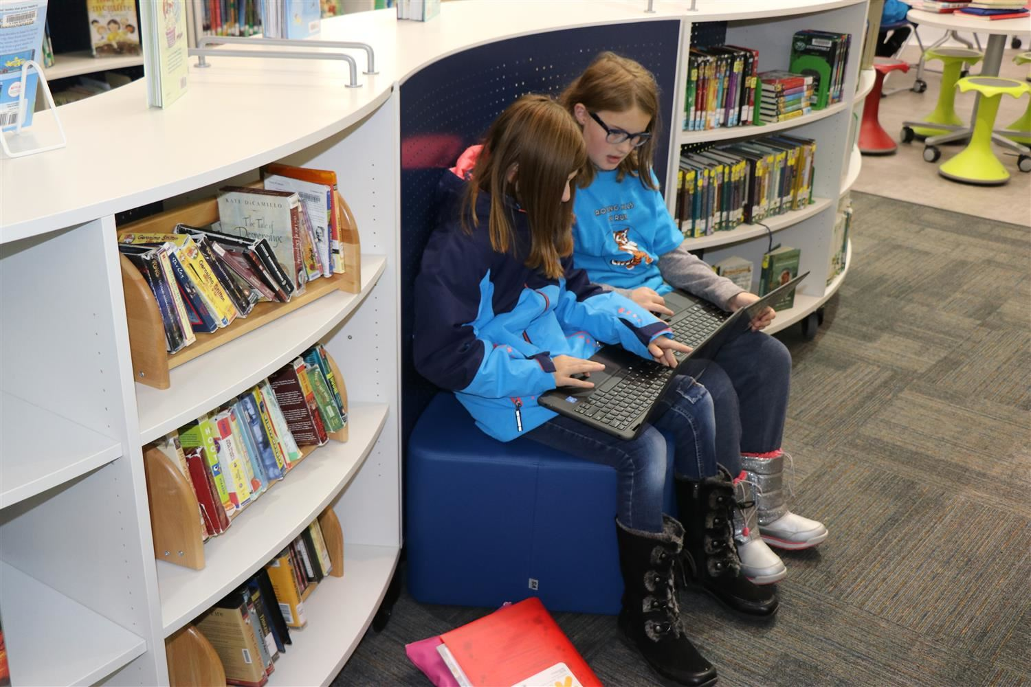 Students work on laptops in a nook inside a bookshelf in newly renovated innovation space.