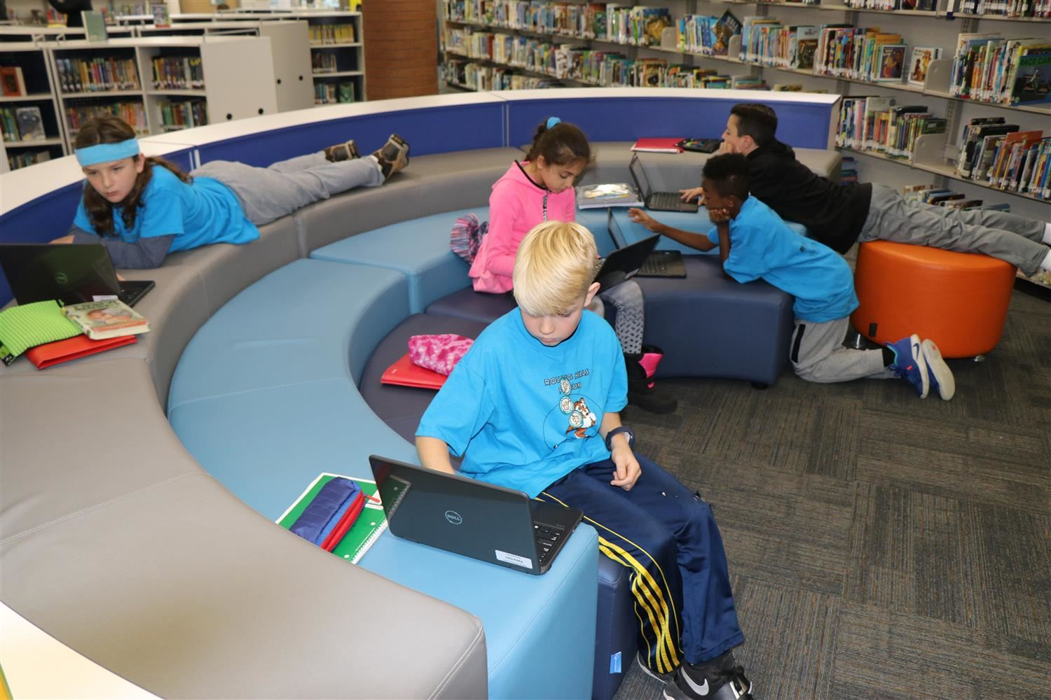 Students spread out in stadium style seating in the school's newly renovated innovation space.