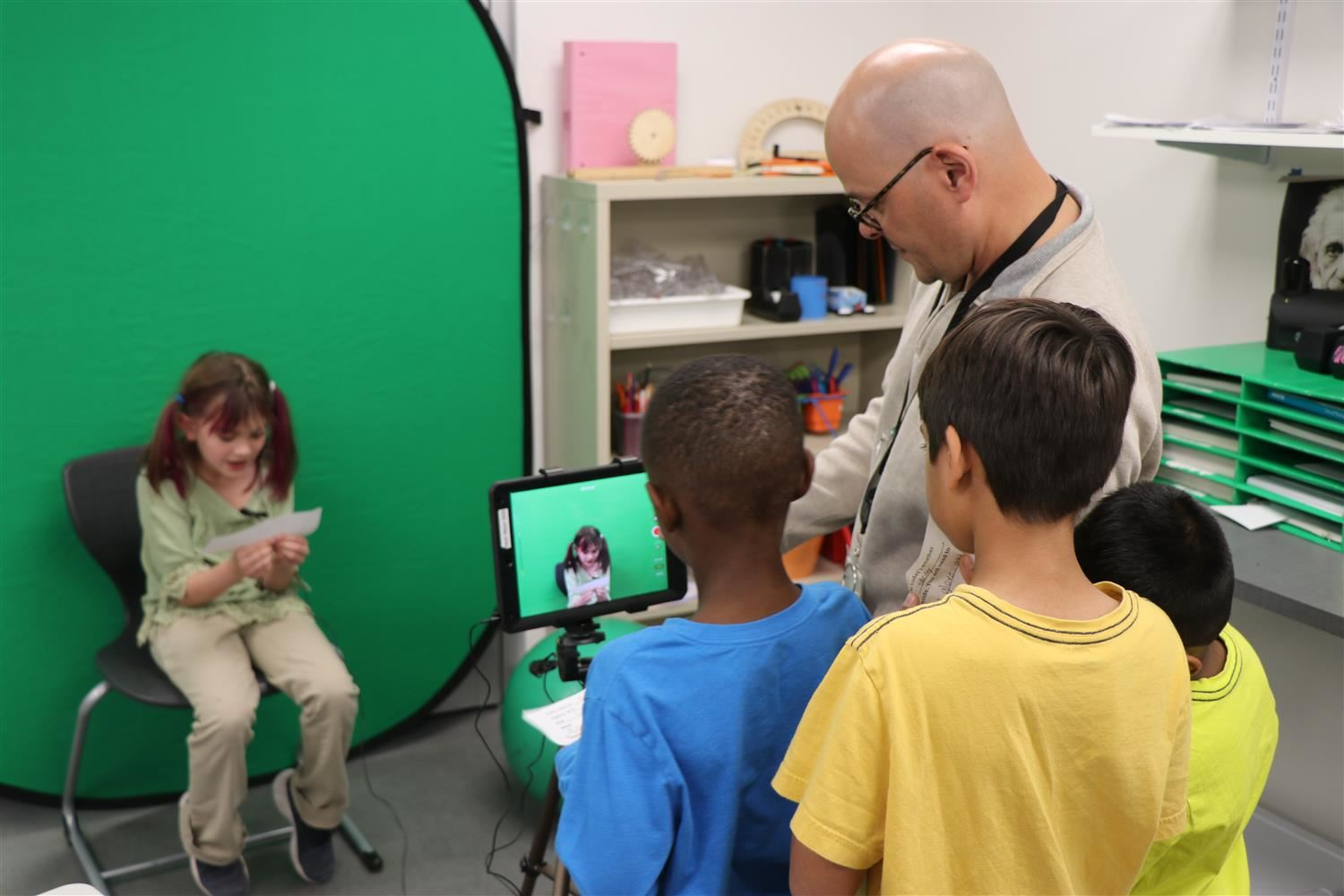 Students view image on IPAD will filming using a green screen.