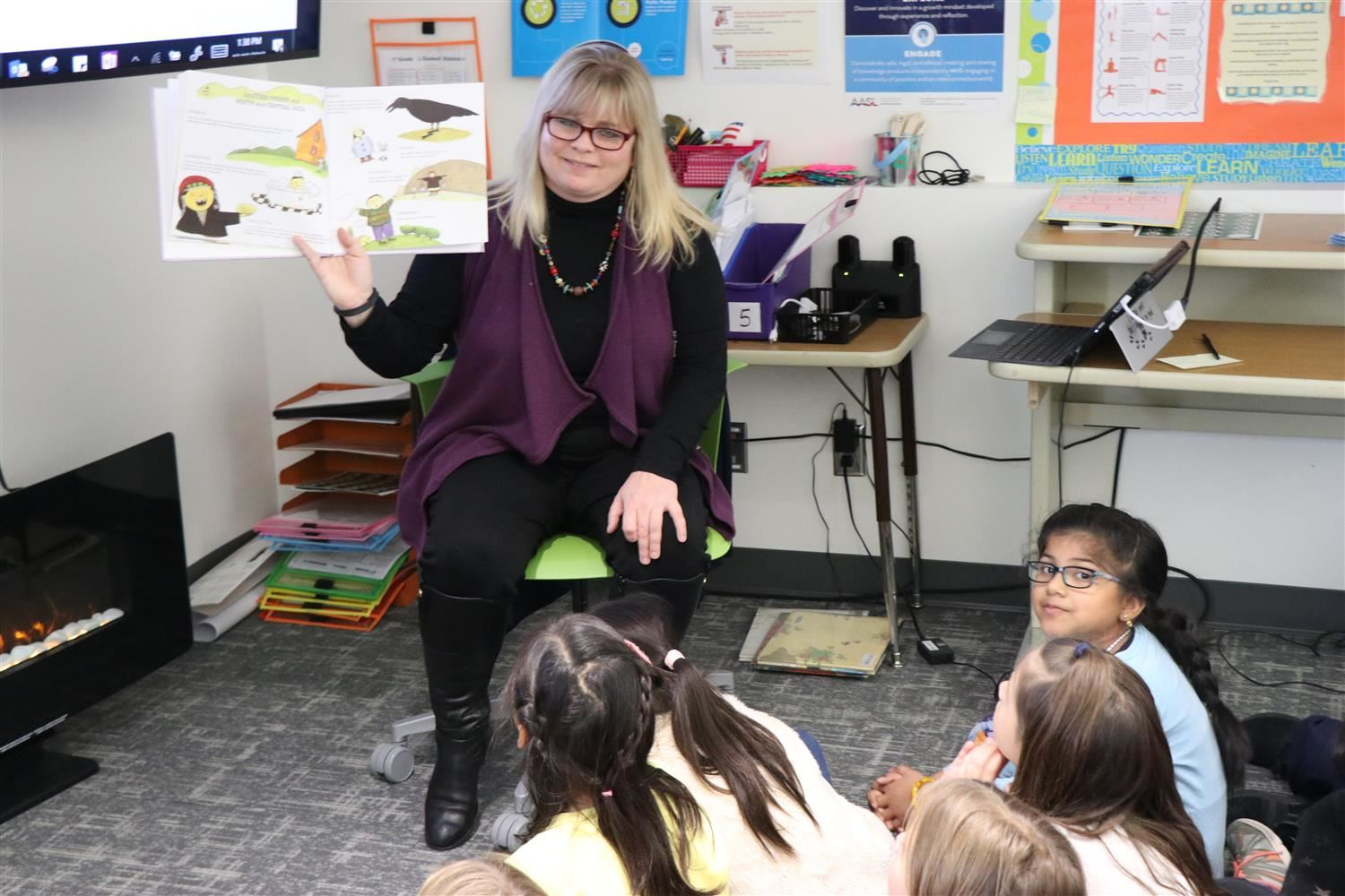 Principal Tiffany Kophs reads a book to students.