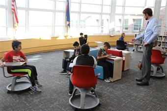 Principal works with students in new innovation space.