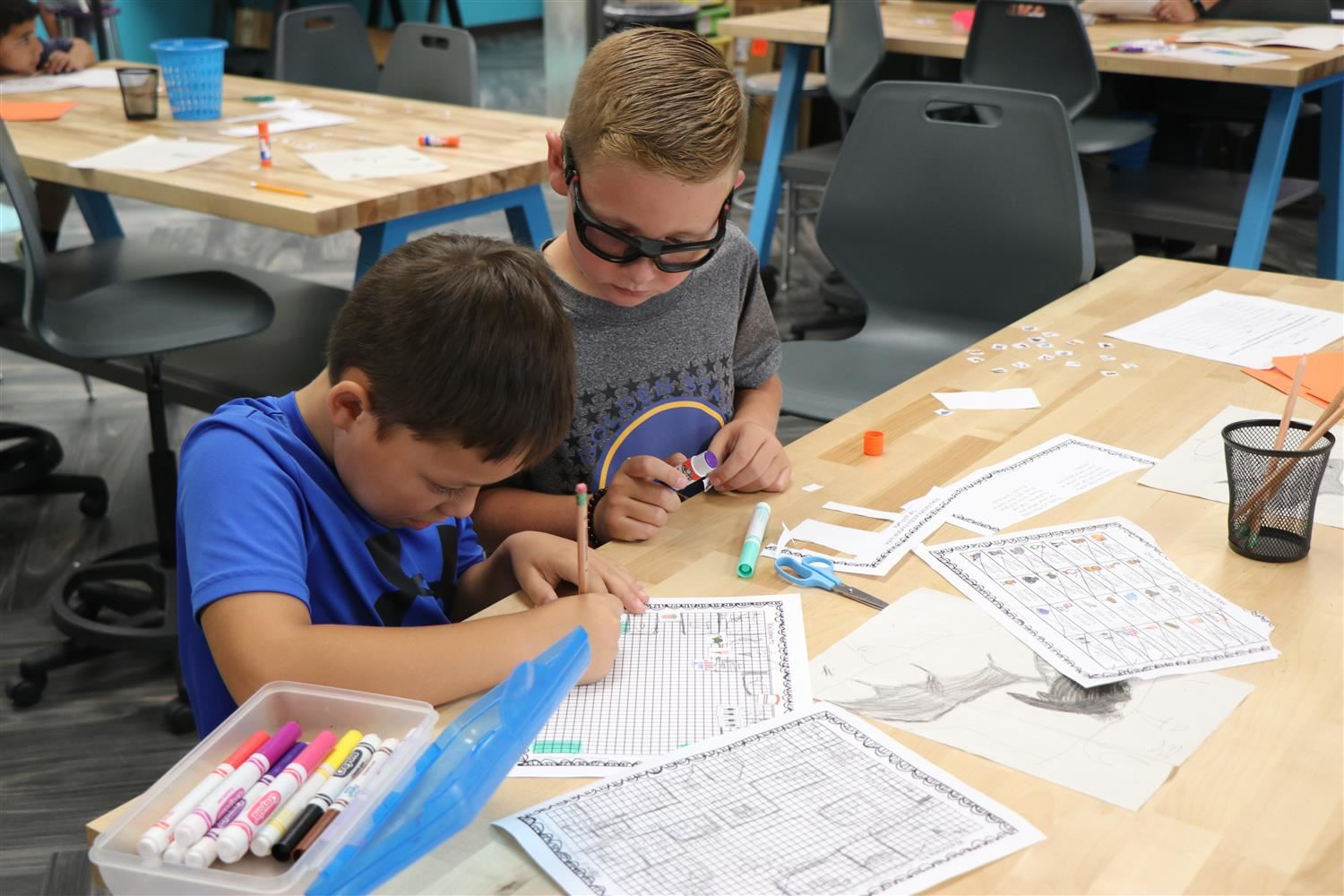 Two boys work on designing a zoo on a table in their new maker space.