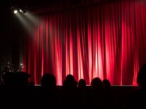 spot light on closed theatre curtain with audience members visible