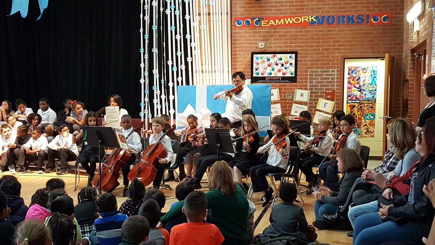 Students playing instruments at a school orchestra concert