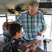 Bus driver David Busse and student discuss origami