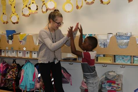 Kaley Kemp high fives with student