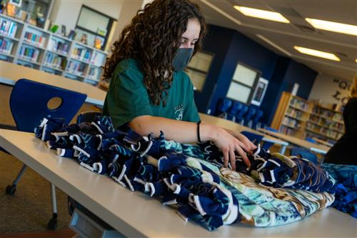 A student at Fox Ridge folds blankets on March 3.