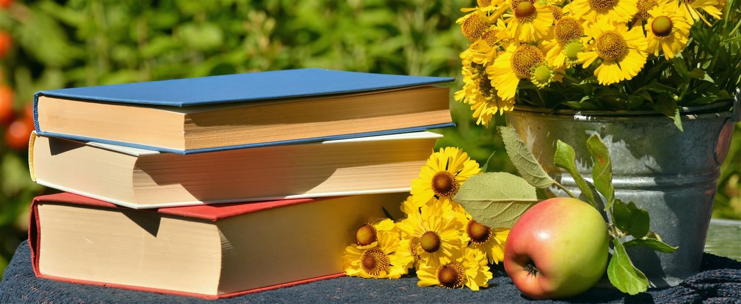 Three books beside bouquet of yellow flowers