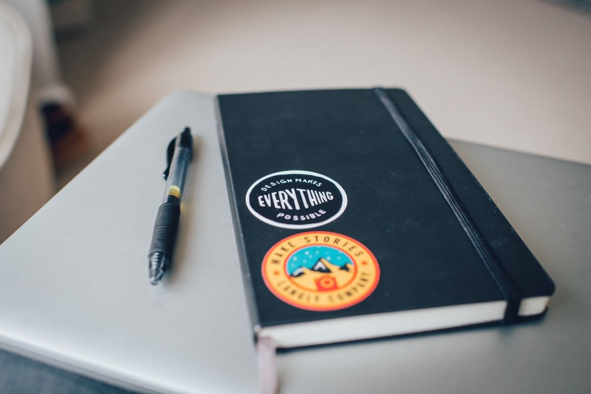 Pen beside notebook with a sticker that says Design makes everything possible