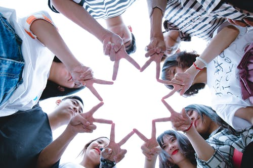 Group of students with fingers touching to create the shape of a star
